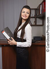 Portrait of a cute young business woman smiling, in an office environment with documents