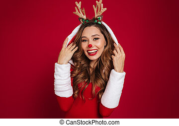 Portrait of a cute young girl wearing christmas deer costume...