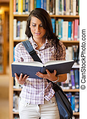 Portrait of a cute young student reading a book