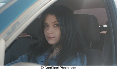 portrait of a cute young woman sitting in a car behind the wheel on the driver's seat.