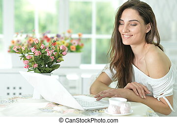Portrait of a cute young woman with laptop