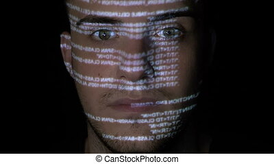 Portrait of a dangerous hacker cyber criminal looking at the camera while running programming code is projected on his face