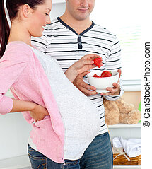 Portrait of a delighted pregnant woman eating strawberries and of her husband at home