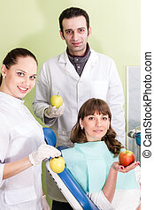 Portrait of a dental assistant and patients with apples