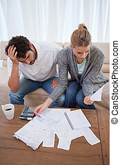 Portrait of a depressed couple doing their accounting in...
