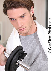 Portrait of a determined man lifting a dumbbell