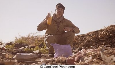 portrait of a dirty homeless hungry man in a dump drinks the...