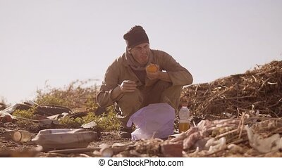 portrait of a dirty homeless hungry man in a dump eating...