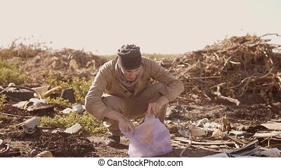 portrait of a dirty homeless man in a dump drinks the...