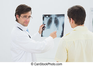 Portrait of a doctor explaining lungs x-ray to patient
