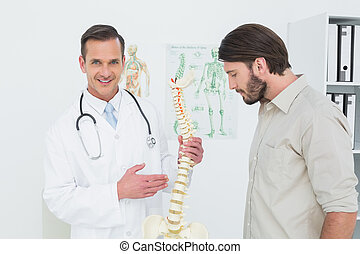 Portrait of a doctor explaining the spine to a patient