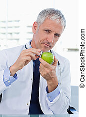 Portrait of a doctor putting his stethoscope on an apple