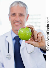 Portrait of a doctor showing an apple