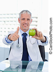 Portrait of a doctor showing an apple with the thumb up