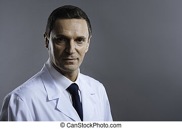 Portrait of a doctor standing on grey background