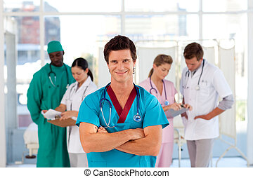 Portrait of a doctor with folded arms in front of  his team
