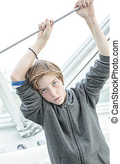 portrait of a dreamy male teenager holding a wire cable with both hands.