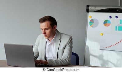 Portrait of a European male sitting at a laptop in the office with a white shirt on the background of graphs and tables