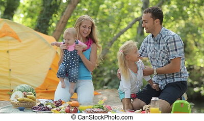 Portrait of a family consisting of parents and two lovely daughters having fun on nature