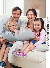 Portrait of a family looking at a photo album