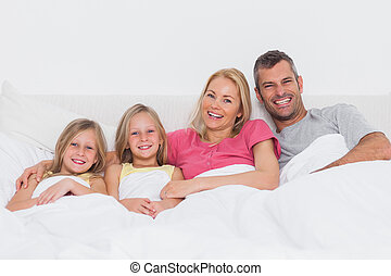 Portrait of a family lying in bed