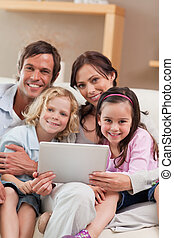 Portrait of a family using a tablet computer in a living...