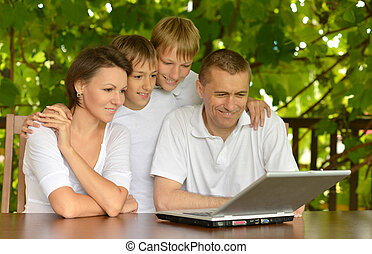 Portrait of a family using laptop together outdoors