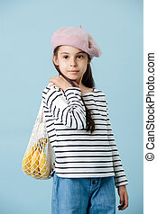 Portrait of a fashionable little girl in french beret holding bag with bananas