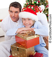 Portrait of a father and his son holding Christmas presents