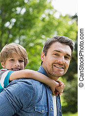 Portrait of a father carrying young boy on back