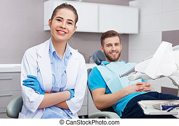 Portrait of a female dentist and young happy  male patient.