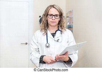 Portrait of a female doctor holding her patient chart
