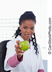 Portrait of a female doctor showing an apple