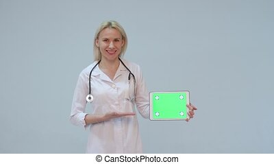 Portrait of a female doctor with white coat and tablet and stethoscope smiling looking into camera