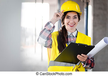 Portrait of a female engineer at construction site and with a clipboard in hands