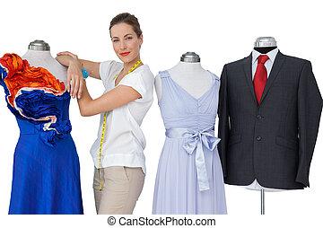 Portrait of a female fashion designer and mannequins...