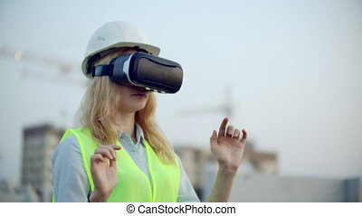 Portrait of a female inspector analyzing the work of builders using virtual reality glasses. A woman in a helmet and a protective vest stands in VR glasses and moves his hands