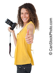 Portrait of a female photographer gesturing thumbs up
