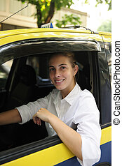 portrait of a female taxi driver driving her new cab