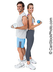 Portrait of a fit couple exercising with dumbbell