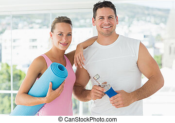 Portrait of a fit couple holding water bottle and exercise mat in bright exercise room