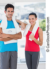 Portrait of a fit couple in bright exercise room