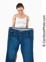Portrait of a fit woman showing large jeans