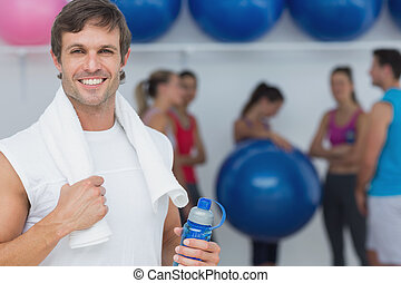 Portrait of a fit young man holding water bottle with friends in background at fitness studio