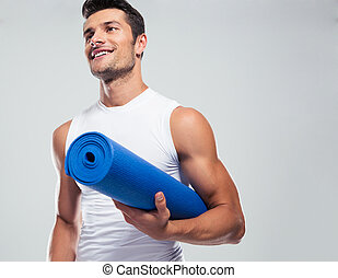 Portrait of a fitness man with yoga mat standing over gray ...