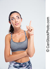 Portrait of a fitness woman pointing finger up