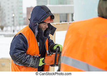 Portrait of a fitter in a vest with a chainsaw in his hands