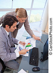 Portrait of a focused business team looking at a graph in an...