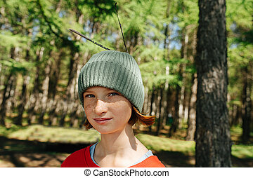 Portrait of a freckled girl in a forest with feathers in her cap.