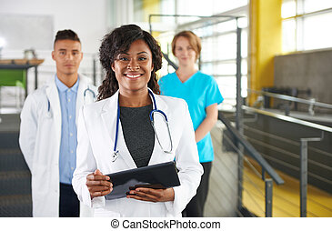Portrait of a friendly female african american doctor and...